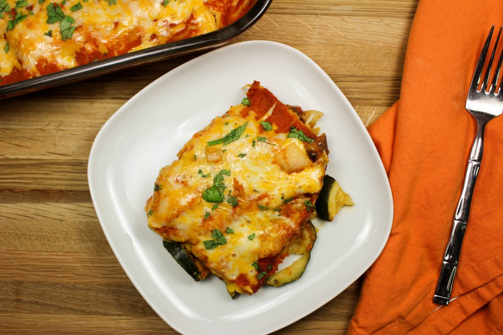Cheesy Vegetable Enchilada Casserole is everything you love about enchiladas. Layers of enchilada sauce, delicious seasoned vegetables, and tortillas topped with cheese. Weight Watchers friendly recipe! www.bitesofflavor.com