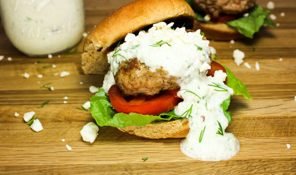 Greek Turkey Burgers are quick to make, packed with spices, and healthy. Top with homemade tzatziki sauce and feta cheese for a delicious Greek inspired burger! Weight Watchers friendly recipe! www.bitesofflavor.com