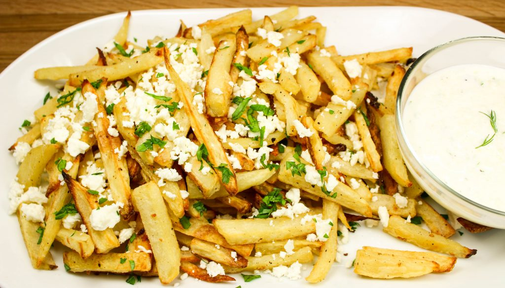 Baked Feta Greek Fries-Perfect lighter version of cheese fries. Crispy baked fries topped with tangy feta cheese. Delicious, easy to make, & the perfect side dish for any meal! Weight Watcher friendly. (4 SmartPoints).