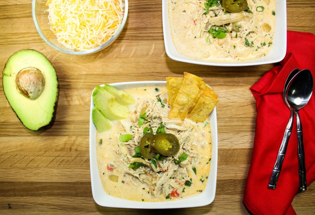 Slow Cooker Jalapeno Popper Chicken Chili as all the flavors of jalapeno popper dip without the guilt. Slow cooked chicken mixed with a creamy broth, white beans, & cream cheese. Not too spicy with just the right kick. Weight Watcher friendly recipe! www.bitesofflavor.com