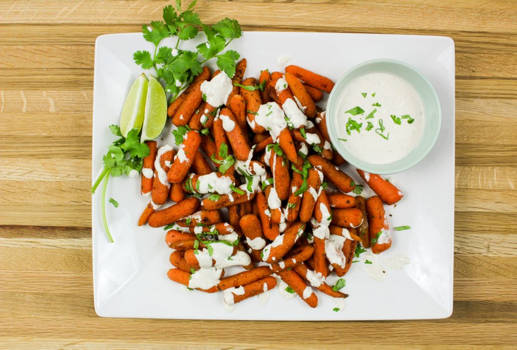 Indian Spiced Carrots with Curry Sauce are a decadent, easy to make side dish perfect for any meal. Roasted carrots coated in Indian spices and served with a creamy curry sauce are delicious with every bite. Weight Watchers friendly recipe! www.bitesofflavor.com