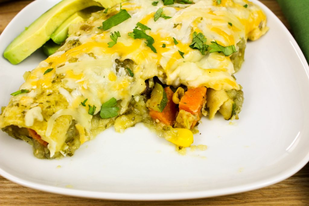 Roasted Tomatillo Vegetable Enchiladas-Packed with fresh, amazing Mexican flavors. Roasted vegetables stuffed in tortillas, coated in fresh tomatillo salsa & topped with cheese is heaven in each bite! Only 8 grams of fat for 2 enchiladas! Weight Watchers friendly (8 SmartPoints).
