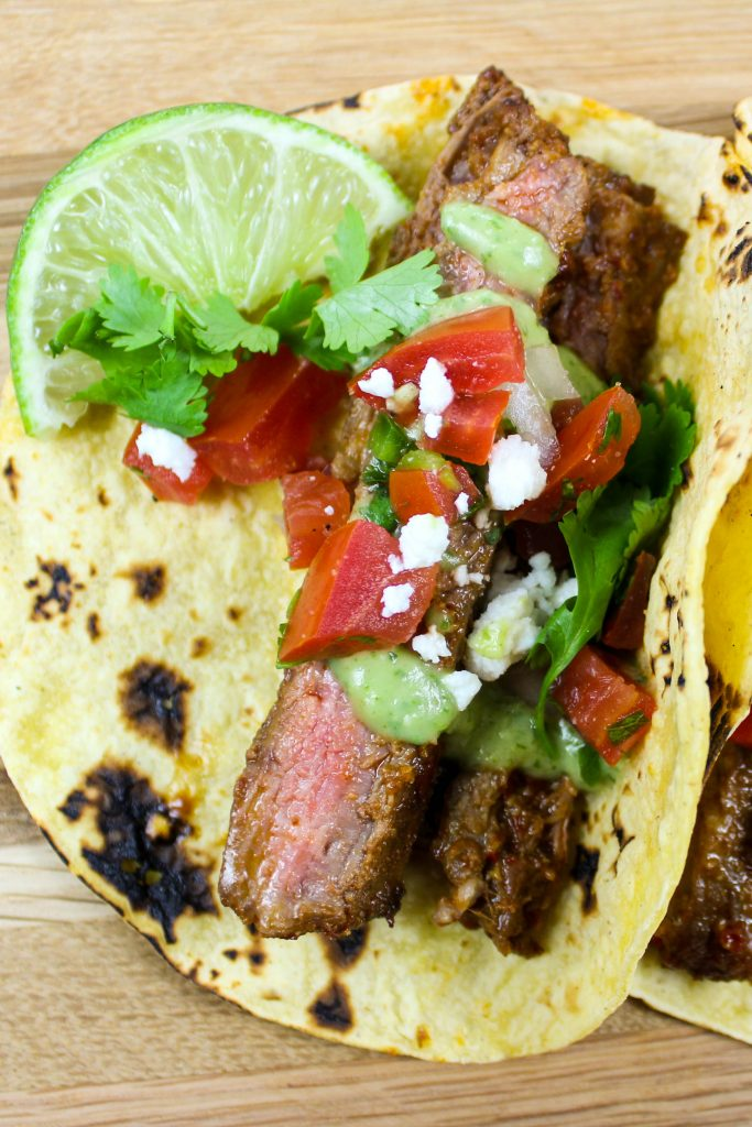 Carne Asada Tacos with Avocado Crema are the perfect way to enjoy steak tacos at home. Marinated lean steak grilled to perfection served in a corn tortilla and topped with fresh Pico de Gallo, Avocado Crema, and Queso fresco. Weight Watchers friendly recipe! www.bitesofflavor.com