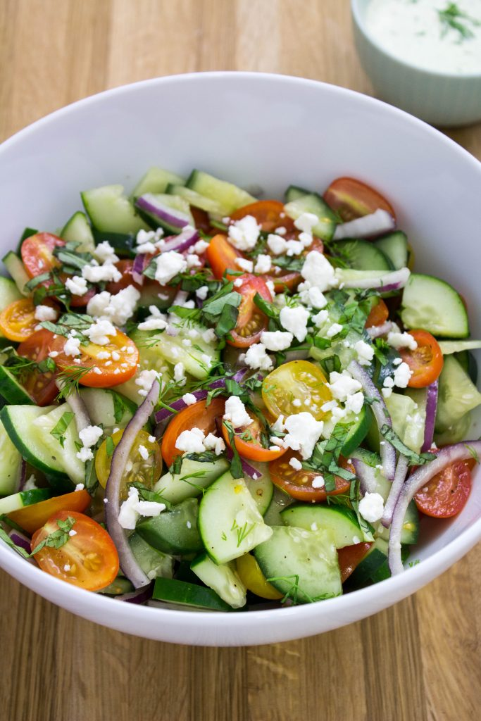 Cucumber Tomato Salad with Herb Vinaigrette- Cucumbers and grape tomatoes tossed in a creamy herb vinaigrette topped with feta cheese. Great for weekday lunch or a picnic! Weight Watchers friendly. www.bitesofflavor.com
