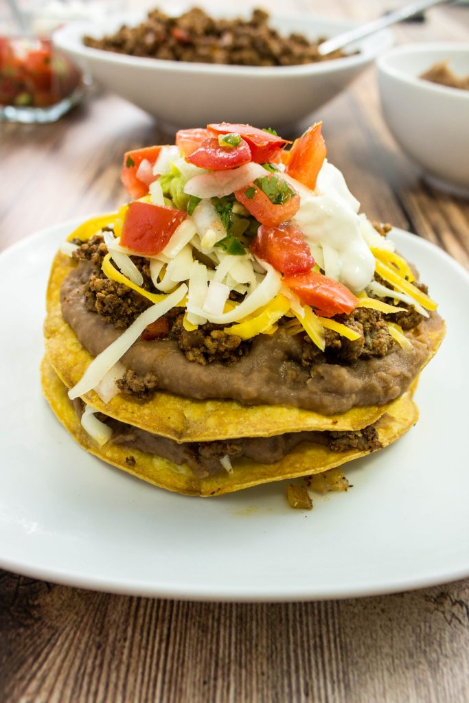 Easy Bean & Beef Tostadas-Taco spiced ground beef & refried beans layered on top of a crispy tortilla topped with cheese & fresh pico de gallo. Weight Watchers friendly. www.bitesofflavor.com