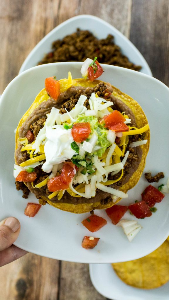 These Easy Bean & Beef Tostadas are made with spiced ground beef & refried beans layered on top of a crispy tortilla. Topped with cheese & fresh pico de gallo. Weight Watchers friendly. www.bitesofflavor.com