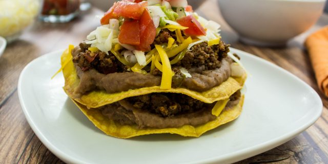 Easy Bean & Beef Tostadas-Taco spiced ground beef & refried beans layers on top of a crispy tortilla topped with cheese & fresh pico de gallo. Weight Watchers friendly. www.bitesofflavor.com