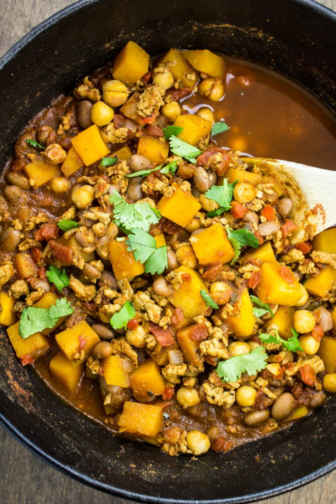 Turkey Bean Chili is a delicious & hearty bowl packed with flavor. Lean ground turkey, peppers, butternut squash, & two kinds of beans cooked in a spicy tomato broth. Easy to make & ready in less than 1 hour. www.bitesofflavor.com