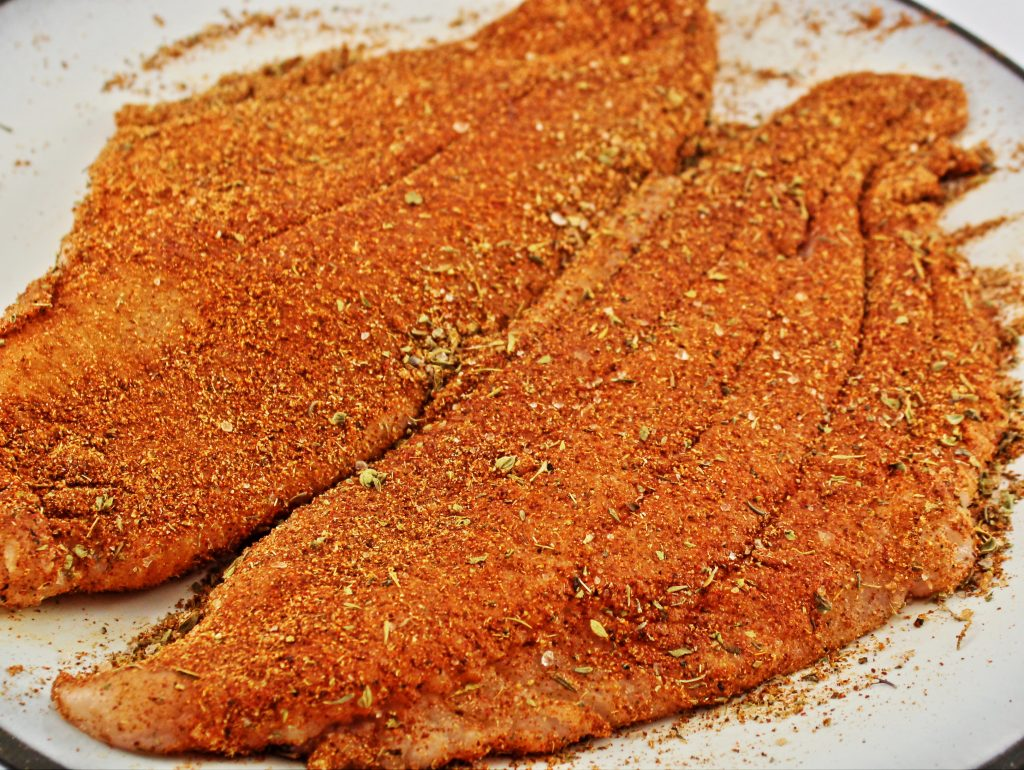 Close up picture of raw catfish that is coated in homemade blackened seasoning