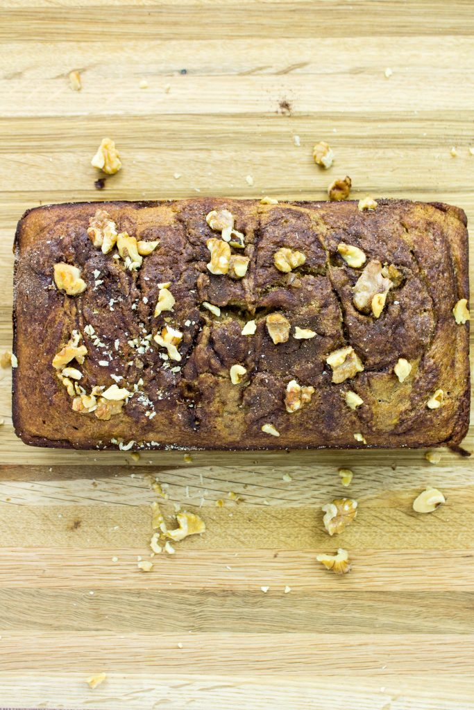 Fluffy banana bread with a cinnamon and sugar swirl in the middle of the bread and on top.