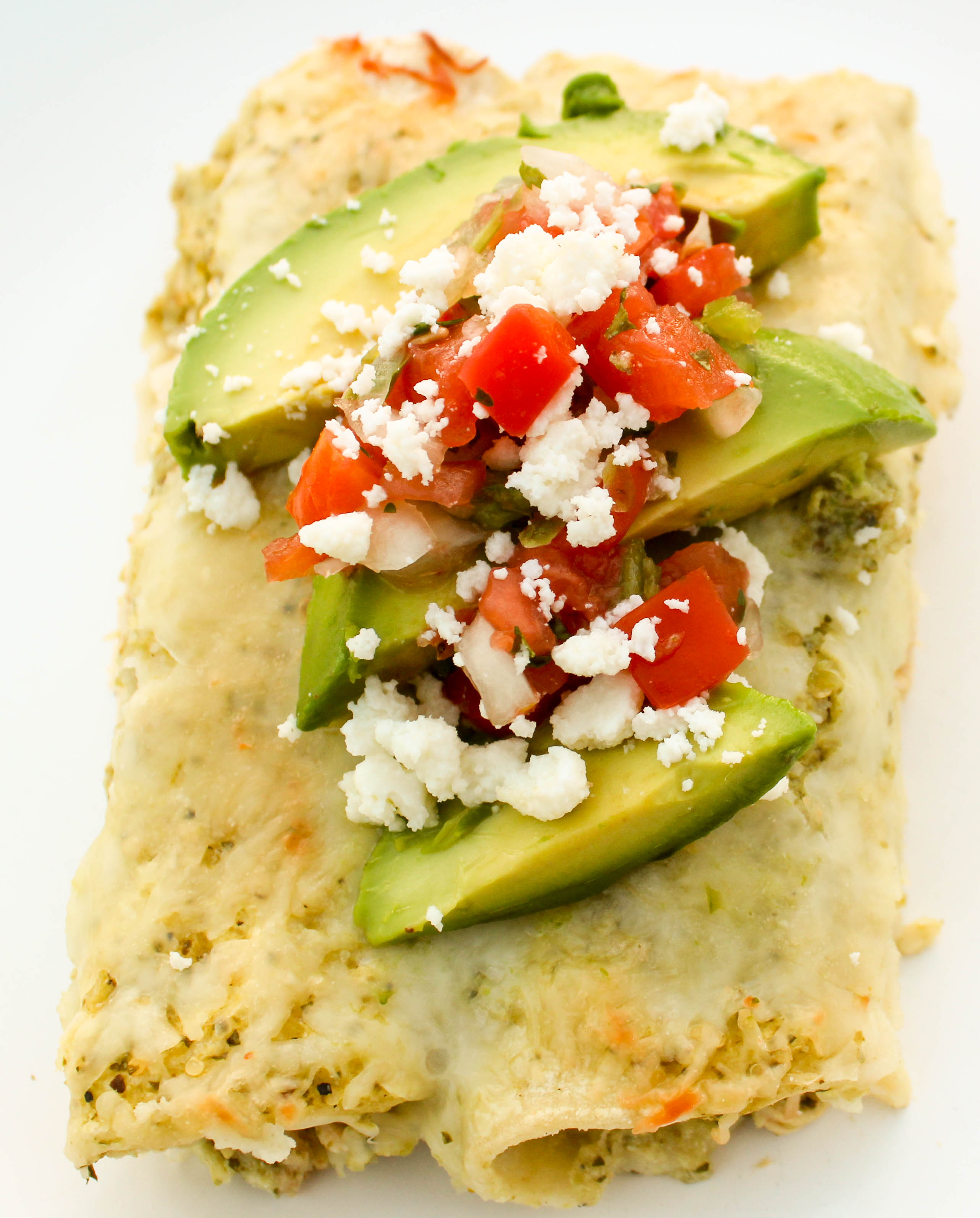 Shredded chicken enchiladas topped with creamy tomatillo salsa and cheese