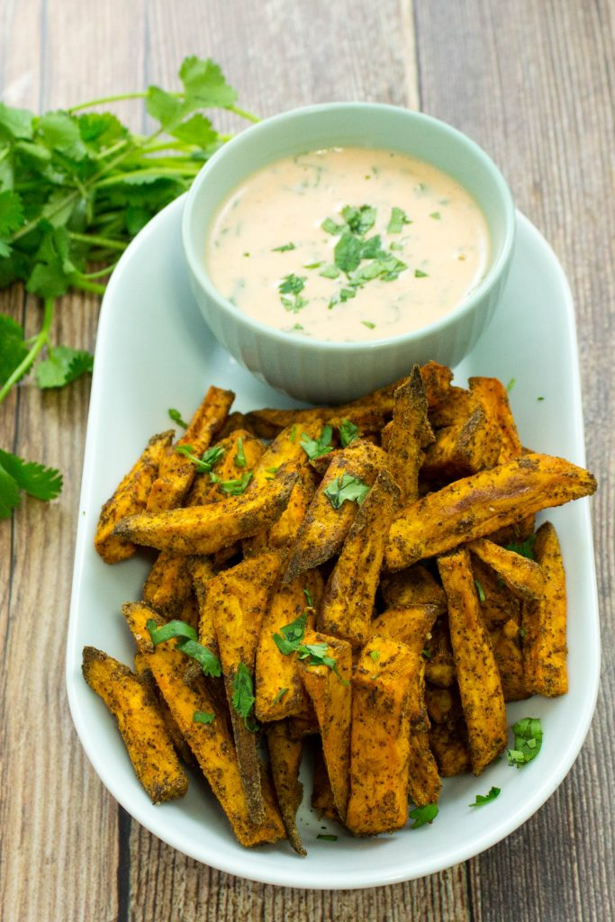 Sweet Potato Fries with Sriracha Aioli is chili spices coated over perfectly baked sweet potatoes & served with a delicious sweet Sriracha aioli. Heaven in every bite. Weight Watchers friendly recipe. www.bitesofflavor.com