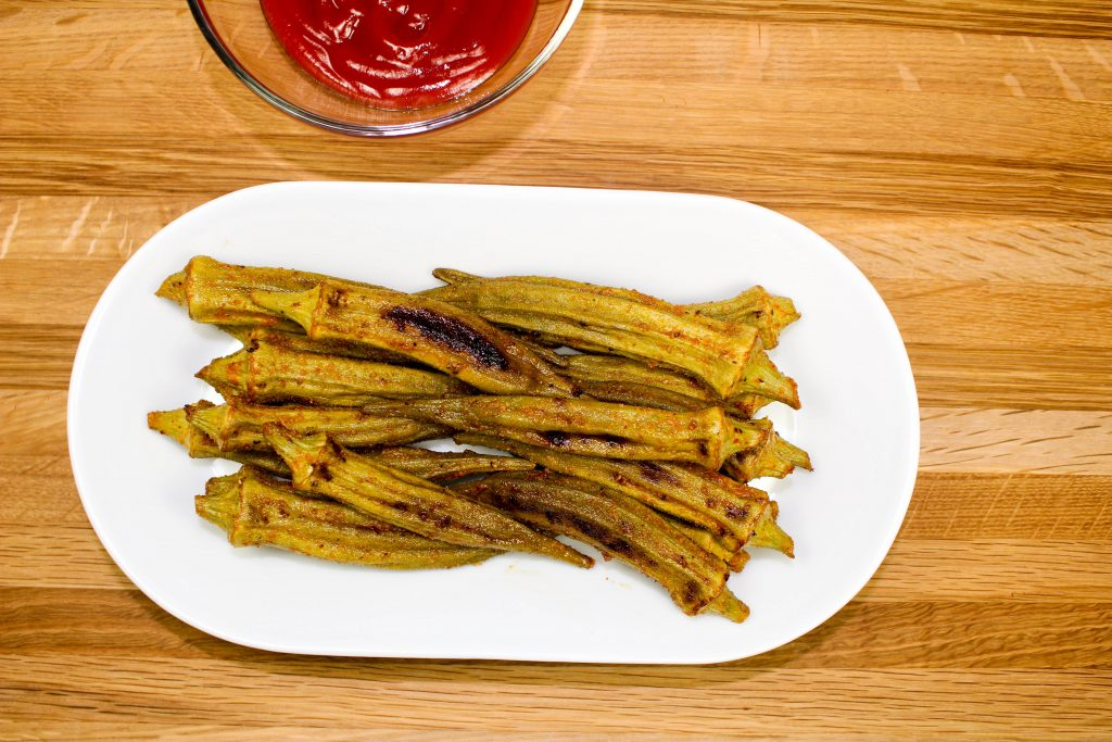 Fresh okra coated in Cajun seasonings and baked in the oven on a plate.