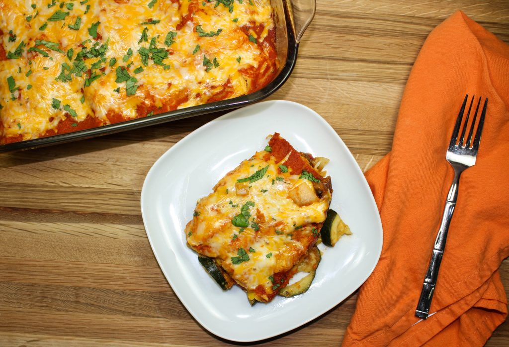 Cheesy Vegetable Enchilada Casserole-Everything you love about enchiladas. Layers of enchilada sauce, delicious seasoned vegetables, and tortillas topped with cheese. Great to feed a crowd and makes for amazing leftovers! Full of flavor and low fat. Weight Watchers friendly recipe! www.bitesofflavor.com