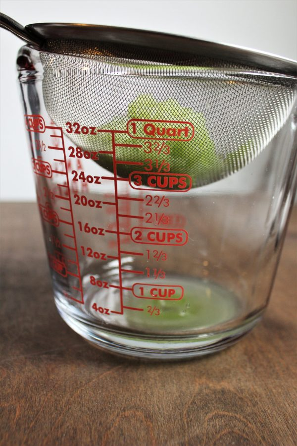 measuring glass with a strainer full of grated cucumbers