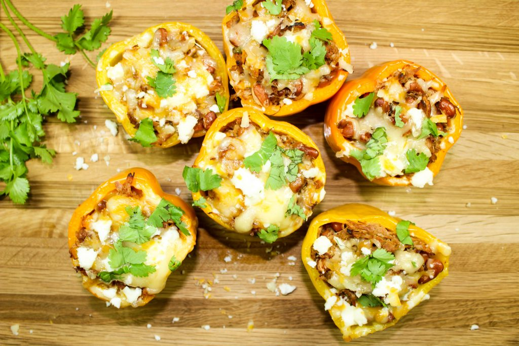 Mexican Spiced Pulled Pork Stuffed Peppers is flavorful Mexican spiced pulled pork and beans stuffed in a pepper and topped with cheese… Delicious & perfect for a quick weeknight meal! Weight Watchers friendly recipe. www.bitesofflavor.com