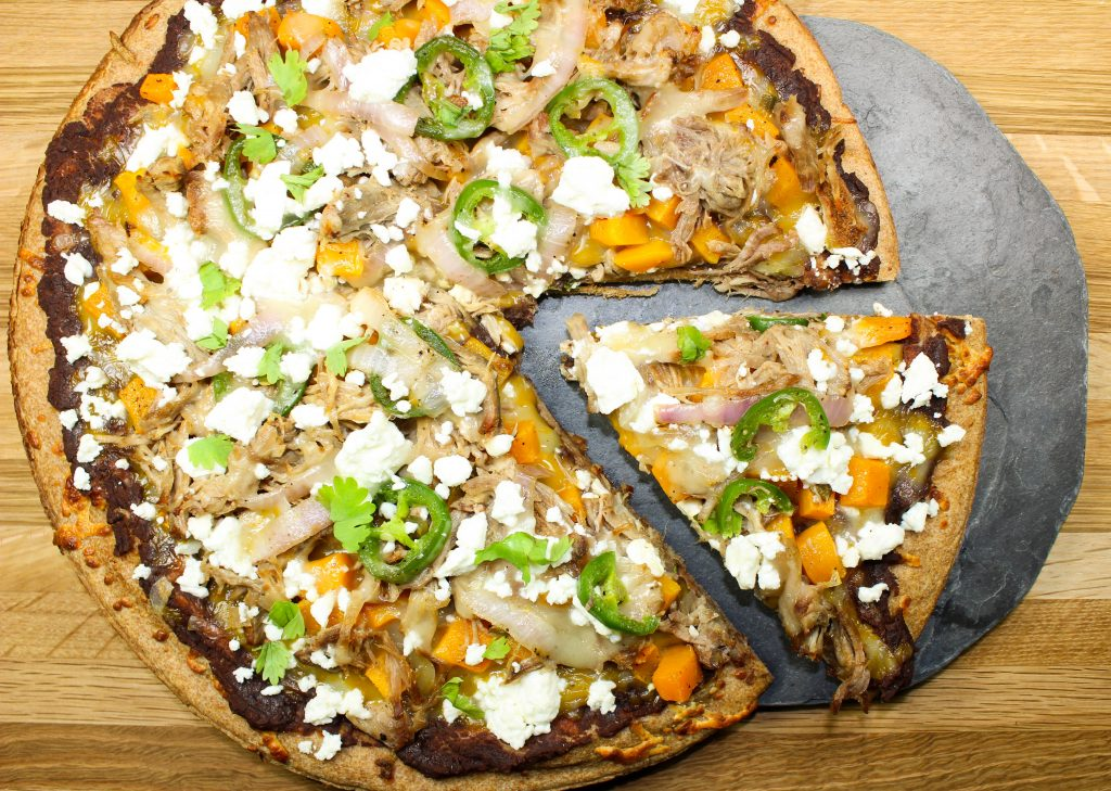 Pulled Pork Mexican Pizza is the perfect pizza to make when you're craving tacos and pizza at the same time. Refried black beans, spiced pulled pork, and cheese make for a great combination. Weight Watcher friendly recipe. www.bitesofflavor.com