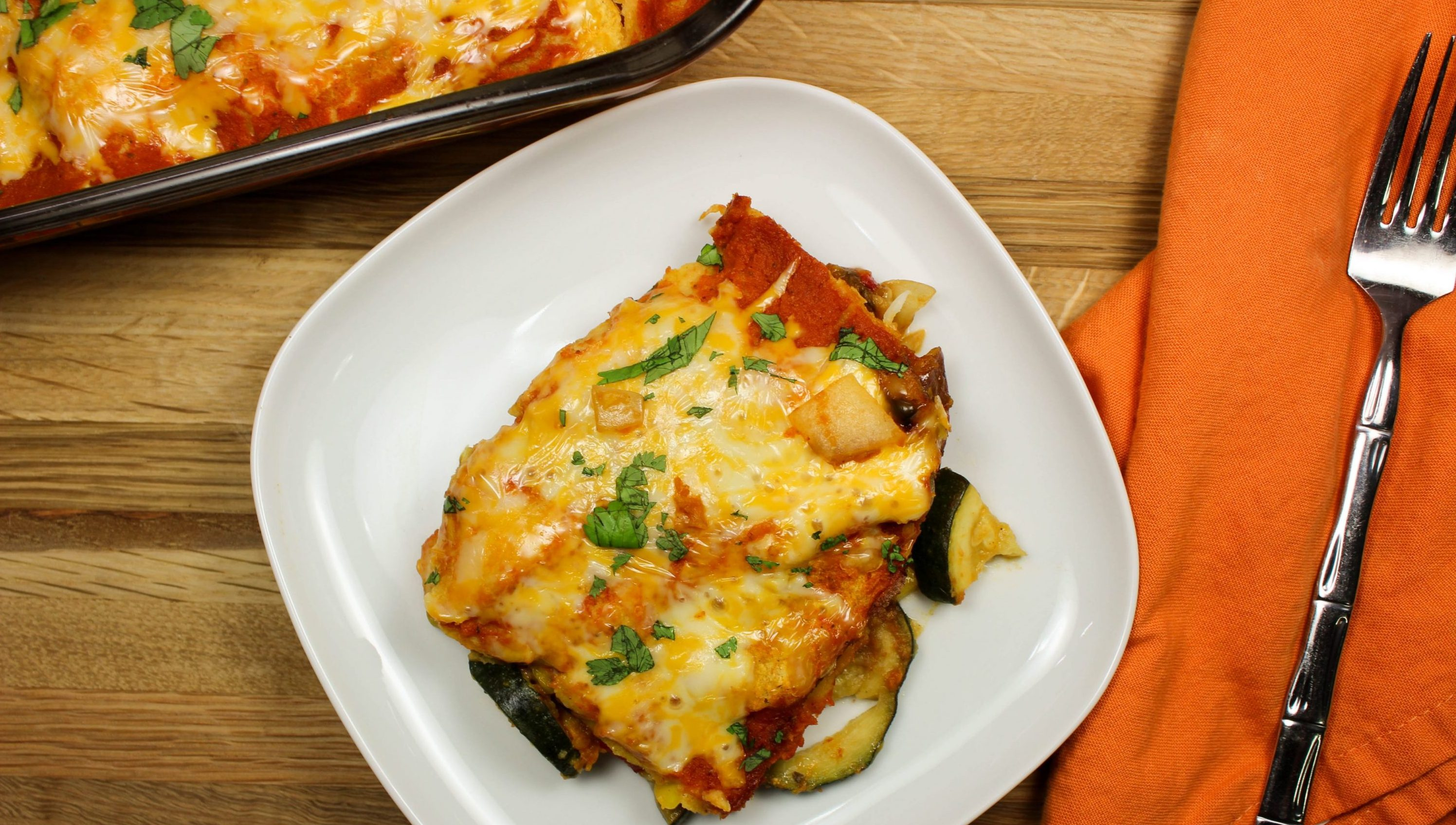 Cheesy Vegetable Enchilada Casserole-Everything you love about enchiladas. Layers of enchilada sauce, delicious seasoned vegetables, & tortillas topped with cheese. Great to feed a crowd & makes for amazing leftovers! Full of flavor & low fat. Weight Watchers friendly