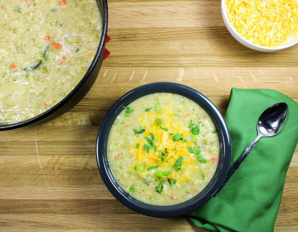 A bowl of homemade broccoli cauliflower chowder topped with cheese.