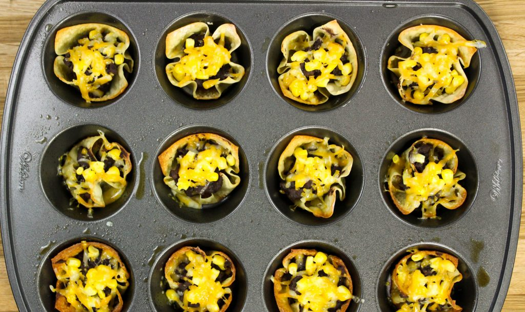 baked wonton wrappers in a muffin tin stuffed with refried black beans and cheese