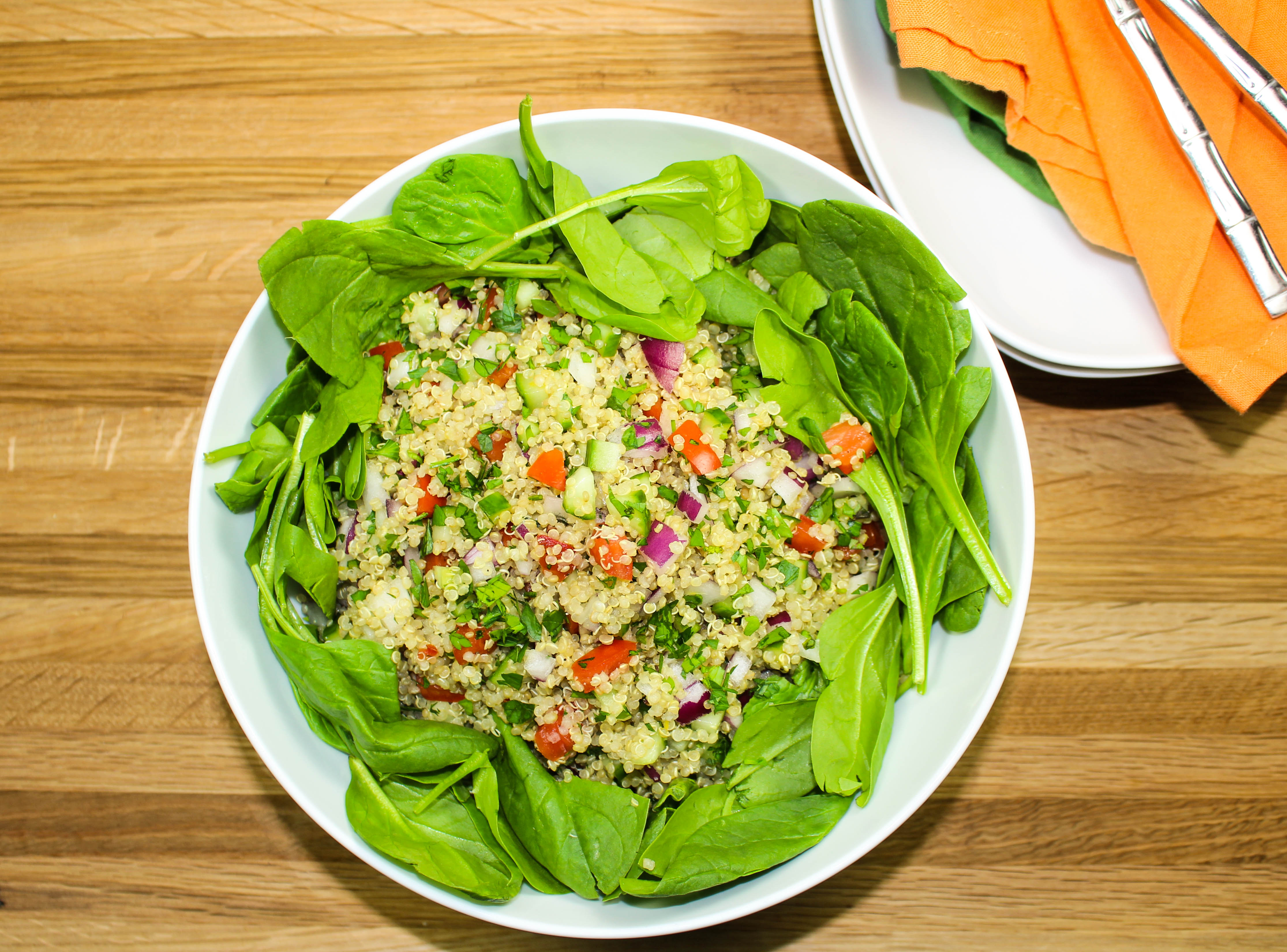 Quinoa Tabbouleh Spinach Salad is fresh vegetables, quinoa & baby spinach, topped with a vinaigrette is sure to please any non-salad lover! Great for make ahead meal. Weight Watchers friendly recipe. www.bitesofflavor.com