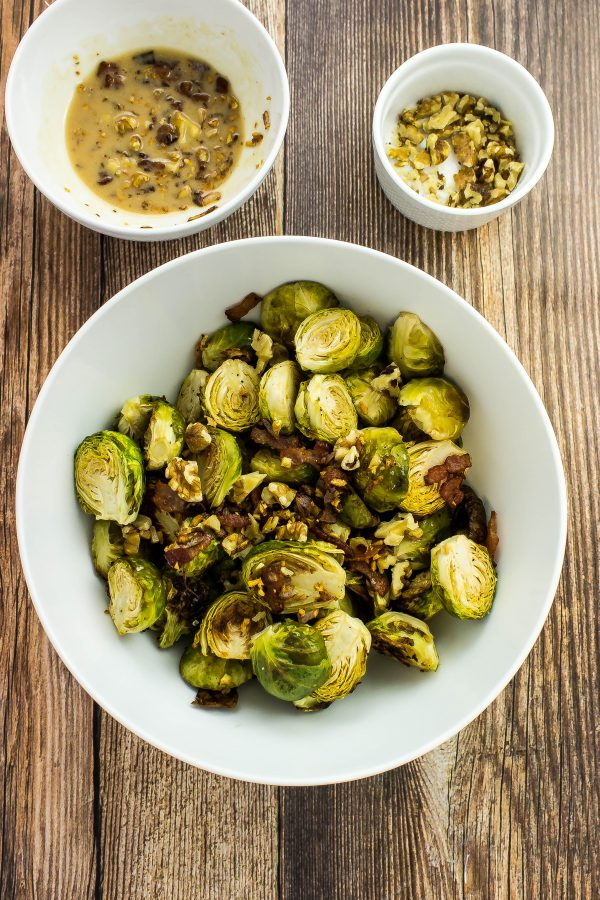 Bacon Honey Dijon Brussel Sprouts-Dijon sauce mixed with bacon, roasted brussel sprouts & topped with walnuts is tangy, crispy, sweet, & addictive with every bite! Weight Watchers friendly. www.bitesofflavor.com