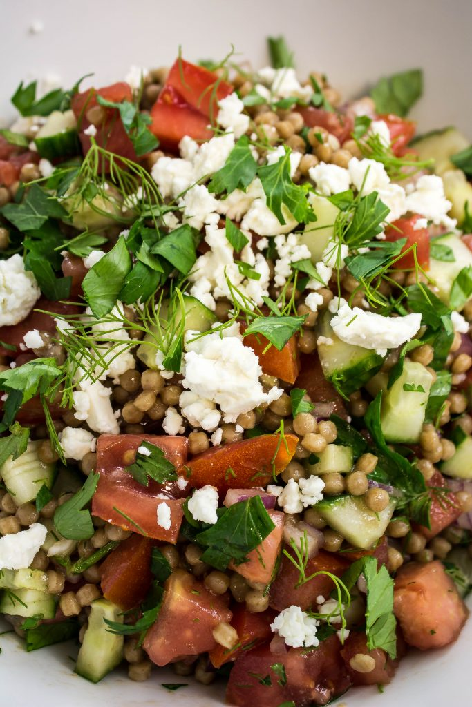 Whole wheat couscous mixed with diced cucumbers, tomatoes, fresh herbs, light dressing, and topped with feta cheese.