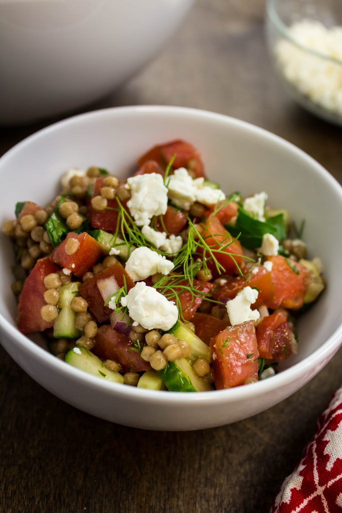Greek Couscous Salad is perfectly cooked whole wheat couscous, fresh tomatoes, cucumber, onion, and herbs mixed with a light vinaigrette.  Weight Watchers friendly recipe!  www.bitesofflavor.com