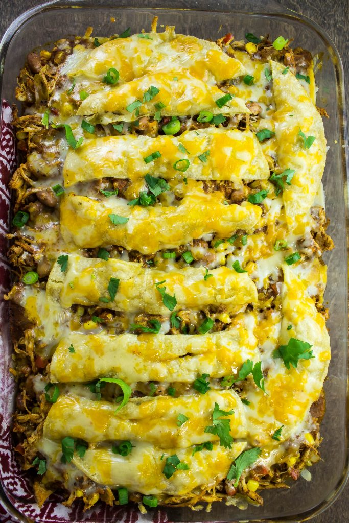 Chicken Tortilla Bake is a delicious tex-mex casserole. Layers of homemade enchilada sauce, tortilla, shredded chicken, beans, peppers, spices, all topped with cheese. Weight Watchers friendly recipe. www.bitesofflavor.com