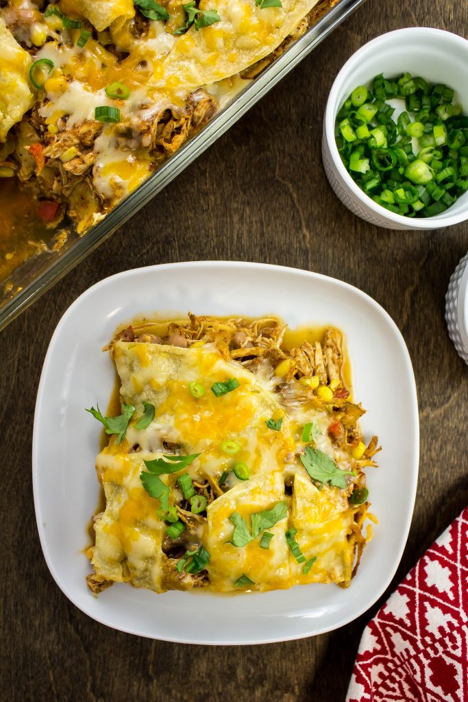 layers of homemade enchilada sauce, tortilla, shredded chicken, beans, peppers, spices, all topped with cheese baked in a casserole dish.