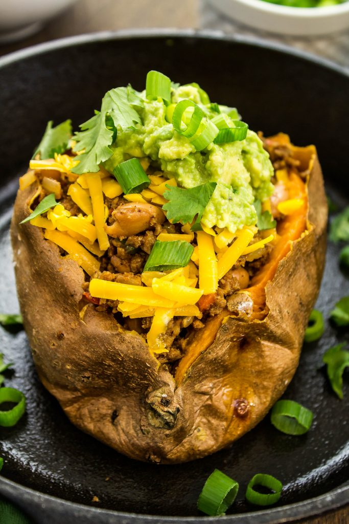 Soy Taco Sweet Potatoes are Taco spiced veggie meat crumbles, sautéed peppers, and beans stuffed into a baked sweet potato with all the fixings! Weight Watchers friendly recipe .