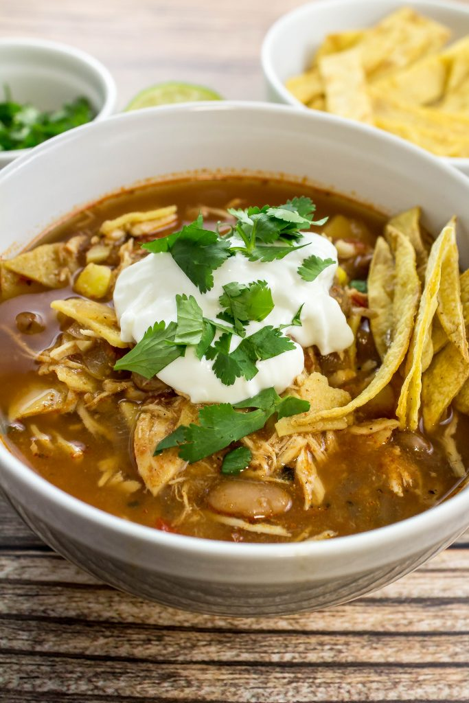 Slow Cooker Chicken Tortilla Soup is tender shredded chicken cooked in a spicy broth for hours with pinto beans and corn is perfect to enjoy year round! So easy to make and freezer friendly! Weight Watchers friendly recipe. www.bitesofflavor.com