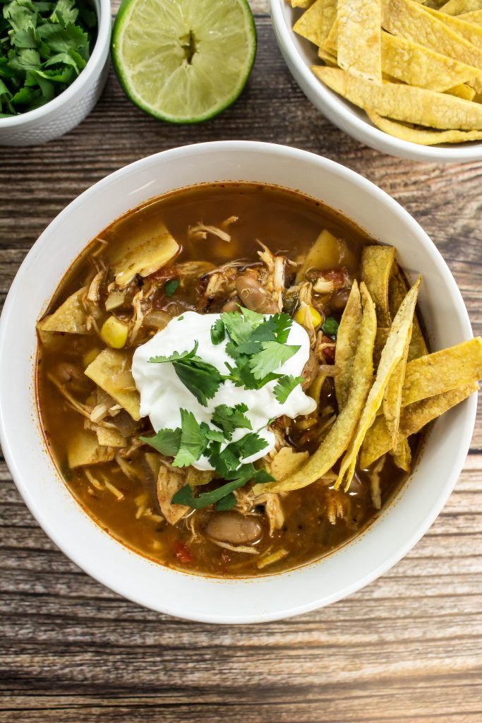 Slow Cooker Chicken Tortilla Soup is delicious comfort in a bowl. Tender shredded chicken cooked in a spicy broth for hours with pinto beans and corn is perfect to enjoy year round! Weight Watchers friendly recipe! www.bitesofflavor.com
